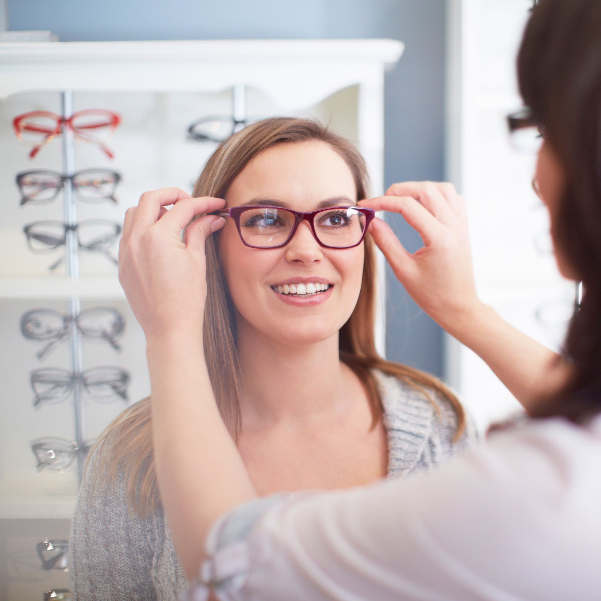 Woman trying on glasses in store.